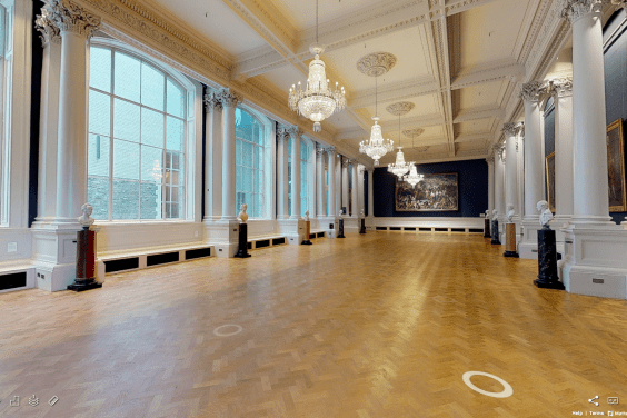A long Gallery with chandeliers, polished wooden floors, and large windows at one side.