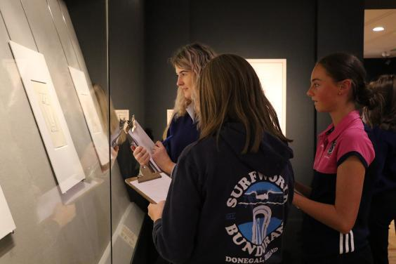 Three teenagers in a print exhibition