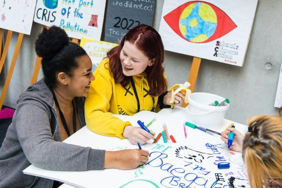 Two teens drawing together at the Creative Schools event in the Gallery
