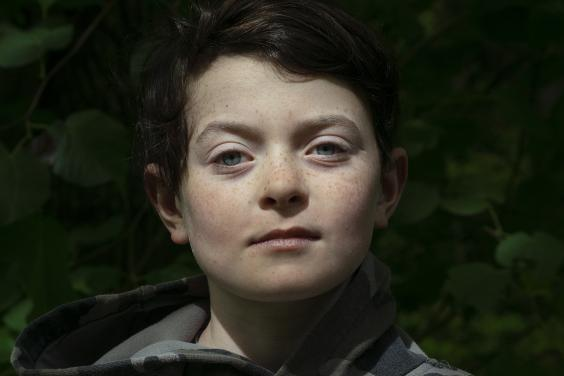 A photographic portrait of a boy. He looks directly at the camera, and is wearing a camouflage hoodie.