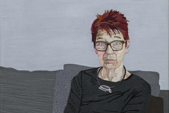 An embroidered portrait of a woman seated on a grey sofa, with her arms crossed in her lap.