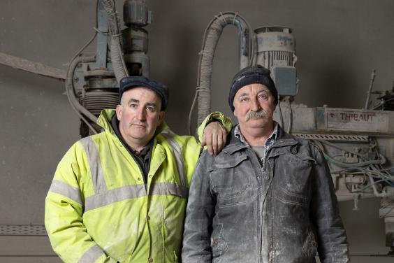 Two men stand in front of industrial-looking equipment. They wear work clothes and boots, and are covered in dust. The man on the left wears a high-vis jacket and rests his hand on the shoulder of the second man.