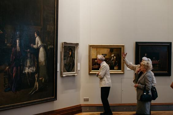 Photo of two women and a man looking at oil paintings in a gallery.