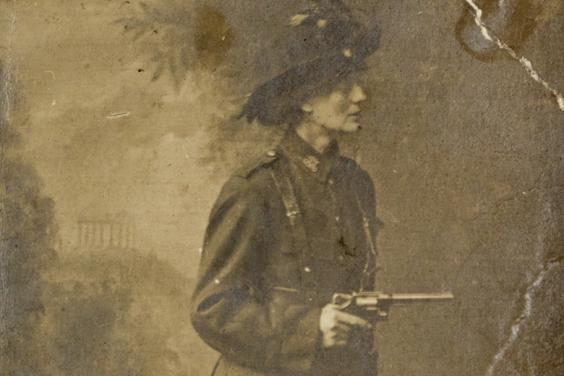 Black and white studio photograph of Constance Markievicz wearing the ICA uniform, posing against a painted backdrop of a landscape and holding a gun.