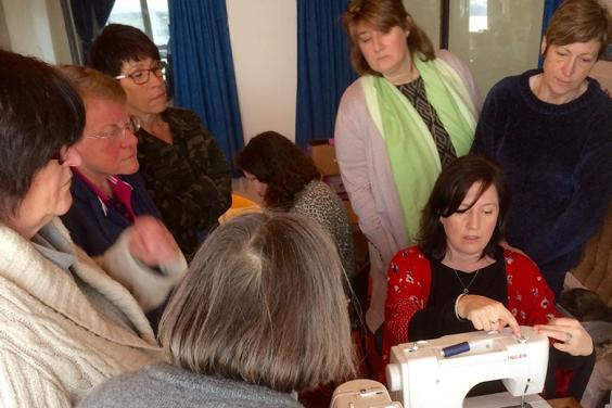 Photo of a group of women watching a seated woman use a sewing machine
