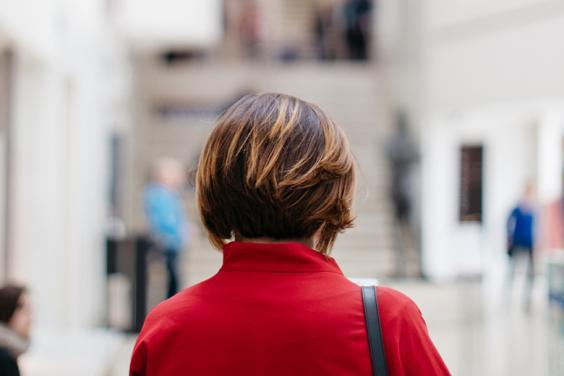 Photo of a woman with her back to the camera, wearing a red coat, standing in the lobby of the Millennium Wing of the National Gallery of Ireland.
