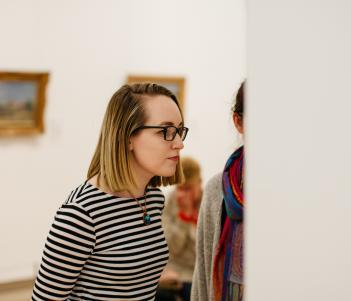 A visitor looking at artworks in the Millennium Wing. © National Gallery of Ireland.