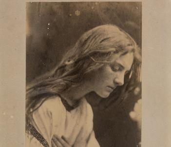 Black and white vintage photograph of a long-haired women with head bowed and hands crossed across chest