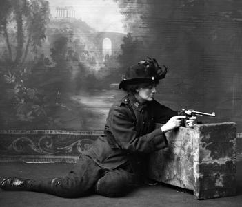 Countess Constance Markievicz in uniform, kneeling against a studio prop holding a gun, studio.