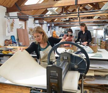 Colour photograph of a printmaking studio with one woman in the foreground running paper through a printing press.