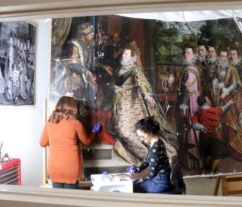 A window into the conservation studio showing conservators at work on Lavinia Fontana's painting