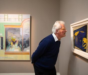 Sean Rainbird looking at a semi-abstract blue and yellow painting of crayfish by Anne Yeats.