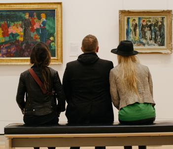 Photo of two women and a man seated on a bench, with backs to camera, looking at two paintings on a white wall.